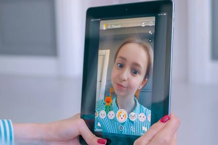 MOSCOW, RUSSIA - MAY 24, 2019: Woman using Snapchat multimedia messaging app with 3d face mask filter on tablet at home. Face detection technology, AR, social media, selfie, entertainment concept