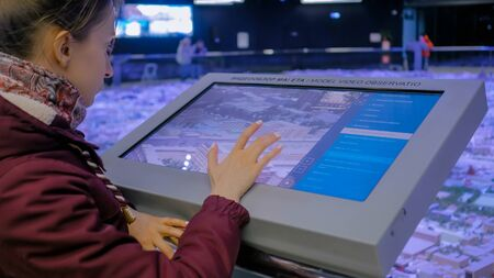 MOSCOW, RUSSIA - JUNE 05, 2019: Smart Expo. Woman using modern touchscreen display of electronic kiosk with interactive 3d architectural model of Moscow. Navigation, journey and technology concept