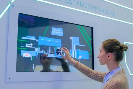 MOSCOW, RUSSIA - JUNE 05, 2019: Smart Expo. Woman using interactive display wall with presentation about russian medical care system and smart medicine at exhibition or museum with futuristic interior