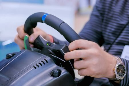 Man gamer hand using black gaming steering wheel joystick and playing in car drive simulator at modern technology exhibition. Entertainment, hobby, technology and leisure time concept