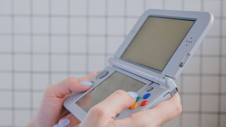 Gaming, hobby, technology, portable, entertainment, video game and leisure time concept. Woman gamer hands using grey handheld game console against tile wall at home - close up side view