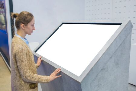 Woman looking at blank interactive white display of kiosk at exhibition, trade show, museum with futuristic sci-fi interior. Mock up, copyspace, template, isolated, white screen, technology concept