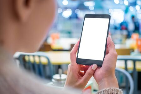 Mockup image: woman looking at black smartphone mobile device with blank white display at cafe, restaurant - close up view. Mock up, white screen, copyspace, template, isolated, technology concept