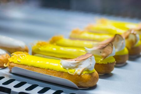 Assortment of delicious fresh cake eclairs with cream for sale on counter of shop, grocery, market, cafe or bakery. Dessert, sweet food, confectionery and traditional french cuisine concept
