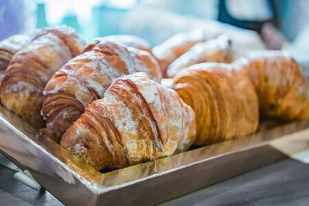 Close up view - assortment of freshly baked croissants for sale on counter of shop, market, cafe or bakery. Dessert, pastry, breakfast, sweet food and traditional french cuisine concept Reklamní fotografie