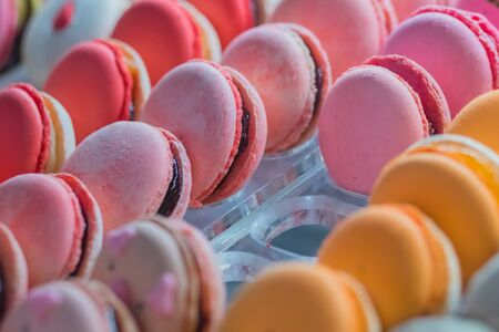 Assortment of colorful macarons cakes for sale on counter of candy shop, market, cafe or bakery. Rows of bright colors macaroons. Dessert, biscuit, sweet food and traditional french cuisine concept Reklamní fotografie