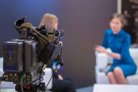 Television video camera recording interview in broadcast news studio. Blurred background. Media, production, TV and broadcast concept Stock Photo
