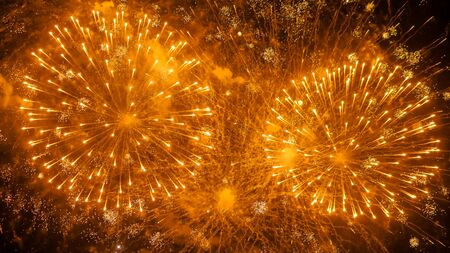 Holiday, celebration and anniversary concept. Colorful bright fireworks in dark sky at night. Evening time, low light illumination