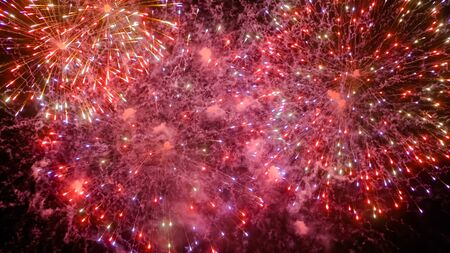 Christmas, holiday, pyrotechnical, celebration and anniversary concept. Colorful bright fireworks in dark sky at night. Evening time, low light illumination