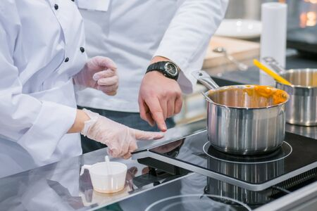 Chef shows how to use electric stove at cuisine of restaurant. Professional cooking, training, education, learning, instruction, catering, cookery, gastronomy and food concept