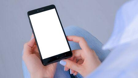 肩の上のビュー:ホームインテリアに白い空白の画面を持つ黒いスマートフォンを持つ女性の手。モックアップ、コピースペース、テンプレート、エンターテイメント、テクノロジーコンセプト 写真素材