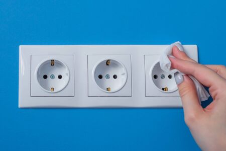 Woman cleaning electrical european outlet, socket with disinfectant wet wipe - close up view. Disinfection, protection, prevention, housework, COVID-19, coronavirus safety and sanitation concept