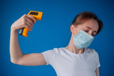 Woman in medical face mask holding yellow pyrometer and showing suicide gesture like pointing gun to head. Shooting, killing oneself, expression, measurement, disease, infection, coronavirus concept