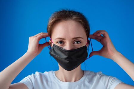 Portrait of woman in white shirt putting on black medical face mask and looking at camera in room with blue wall at home: close up. Self isolation, prevention, quarantine, COVID19, coronavirus concept Stok Fotoğraf