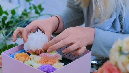 Professional woman floral artist, florist making gift box with flowers at workshop, flower shop. Floristry, handmade and small business concept