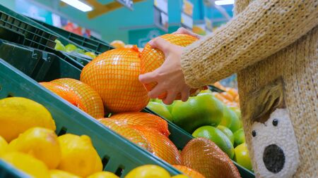 Woman buying fresh exotic citrus fruits - sweetie, sweety, pomelo at supermarket. Close up shot of woman hands. Consumerism, sale, organic and health care concept