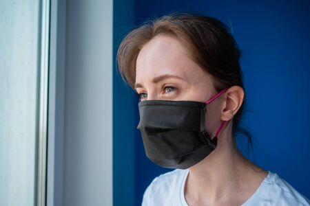 Portrait of pensive woman wearing black medical face mask and looking out of window in room with blue wall at home. Self isolation, prevention, quarantine, COVID-19, coronavirus, safety concept