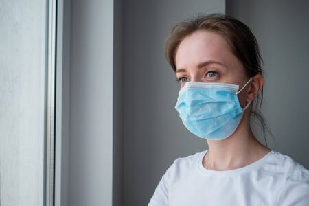 Portrait of pensive woman wearing medical face mask and looking out of window in room with grey wall at home. Self isolation, prevention, quarantine, COVID-19, coronavirus, safety concept