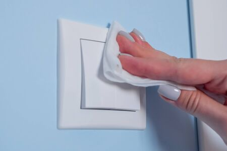 Disinfection, protection, prevention, housework, COVID 19, coronavirus, safety, sanitation concept. Woman hands cleaning white light switch on blue wall with antiseptic disinfectant wet wipe