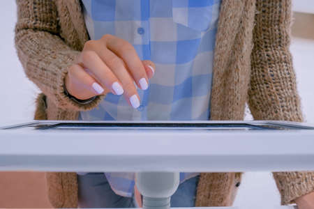 Woman hand using touchscreen display of interactive floor standing white tablet kiosk at exhibition or museum - top close up view. Futuristic, education, entertainment, learning, technology concept