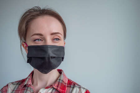 Woman wearing black medical face mask, red plaid shirt, looking away in room with grey wall at home. Self isolation, prevention, quarantine, COVID 19, coronavirus, safety concept