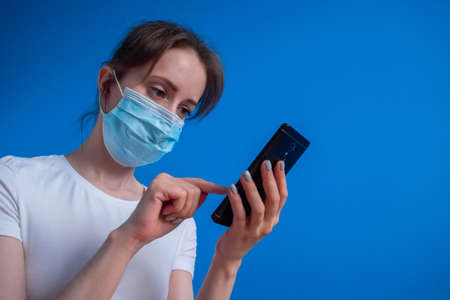 Quarantine, self isolation, technology concept. Portrait of woman wearing medical face mask and using black smartphone with touchscreen display in room with blue wall: scrolling and touching