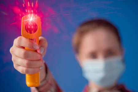Woman in medical face mask holding yellow pyrometer to measure temperature toward camera - close up view, selective focus, lens flare. Healthcare, measurement, disease, infection, coronavirus concept