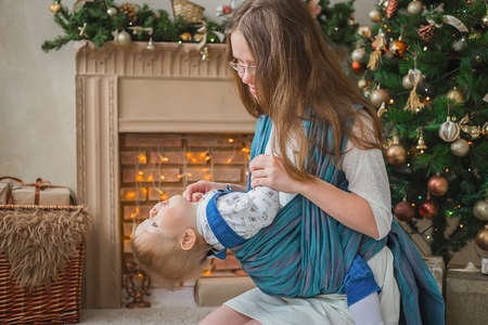 Portrait of young mother carrying baby son in sling against Christmas interior in bright room at home. Family, maternity, holiday, childhood and leisure time concept
