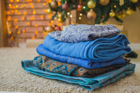 Stack of new colorful cotton scarves against Christmas interior - close up view. Fashion, design, holiday, accessory concept