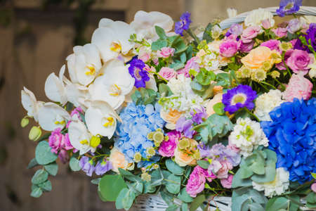 Large floral basket with colorful flowers at workshop, flower shop. Floristry, holiday, romantic, celebration, handmade and small business concept