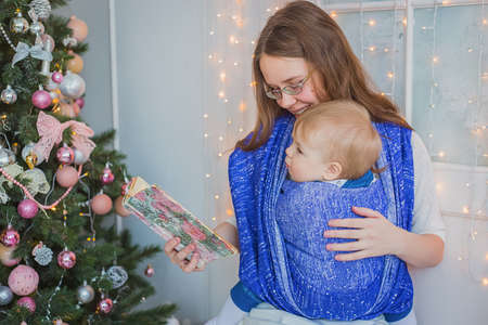 Young mother and her baby son reading book togerher in bright room at home with Christmas interior. Family, holiday, childhood and leisure time concept