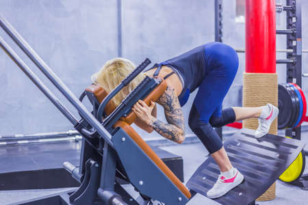 Athletic young woman working out on a fitness exercise equipment at the gym. Health, bodybuilding, training, wellness, lifestyle, sport and workout concept Imagens