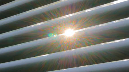 Morning sunrise light, sun lens flare through louvers, jalousie