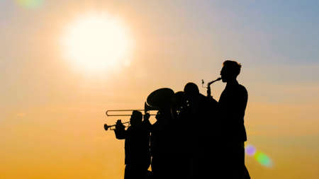 Unrecognizable brass band silhouette playing wind instruments at sunset. Entertainment, music, urban culture and art concept