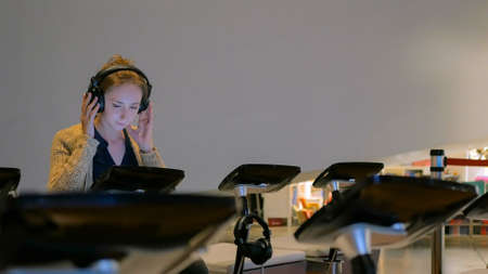 Woman using headphones and listening audio guide at modern history museum. Education and technology concept 版權商用圖片