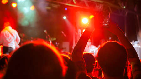 People partying in front of the stage. Unrecognizable hands silhouette taking photo or recording video of live music concert with smartphone. Photography, entertainment and technology concept Stockfoto