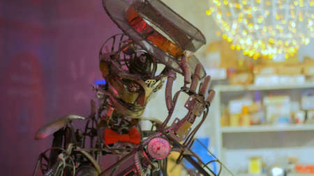 Vintage steampunk robot with cylinder greeting visitors of show. Future and robotic concept Foto de archivo