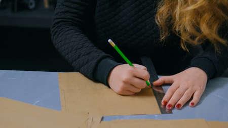 Close up shot - professional woman decorator, designer working with kraft paper and making envelope at workshop, studio. Design, handmade and art concept