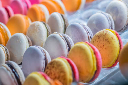 Rows of bright colorful macarons cakes for sale on counter of candy shop, market, cafe or bakery. Dessert, biscuit, sweet food and traditional french cuisine concept