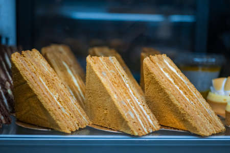 Assortment of delicious fresh layered honey cake pieces with cream and nuts for sale on counter of shop, grocery, market, cafe or bakery. Dessert, sweet food and confectionery concept