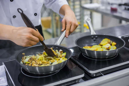 Chef cooking sliced champignon mushrooms, onions and potatoes in frying pans with oil on electric stove at cuisine of restaurant. Professional cooking, catering, cookery, gastronomy and food concept