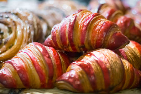 Assortment of freshly baked croissants for sale on counter of shop, market, cafe or bakery. Dessert, pastry, breakfast, sweet food and traditional french cuisine concept Foto de archivo