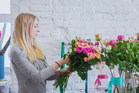 Professional woman floral artist, florist making beautiful fresh wedding bouquet, floral composition in white bright room of workshop, flower shop. Floristry, decor, handmade , small business concept