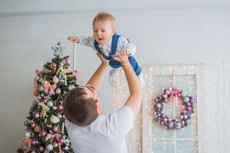Young father throwing up baby son in bright white room with Christmas interior at home. Family, holiday, parenthood, playing, game, childhood and leisure time concept Foto de archivo