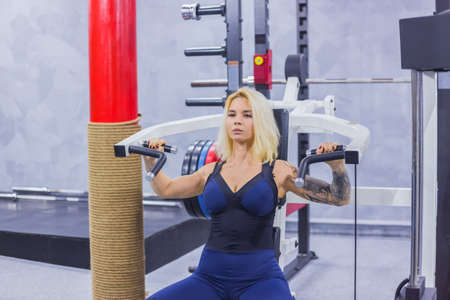 Athletic young woman working out on a fitness exercise equipment at the gym. Health, sport and workout concept Foto de archivo