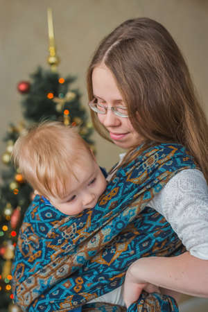 Portrait of young mother carrying baby son in sling against Christmas interior in bright room at home. Family, holiday, childhood and leisure time concept Foto de archivo
