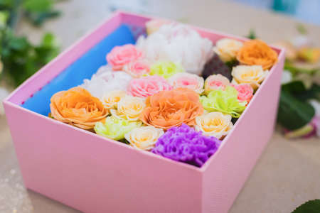Close up view of gift box with colorful flowers - rose, peony, carnation on table at flower shop. Floristry, craft, handmade, wedding, birthday, celebration concept Foto de archivo