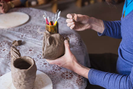 Professional male potter shaping mug in shape of human face with special tool in pottery workshop, studio. Crafting, artwork and handmade concept