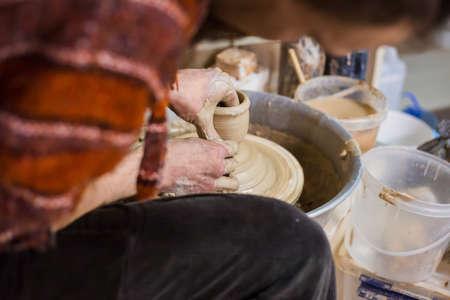 Professional male potter making mug in pottery workshop, studio. Handmade, art and handicraft concept