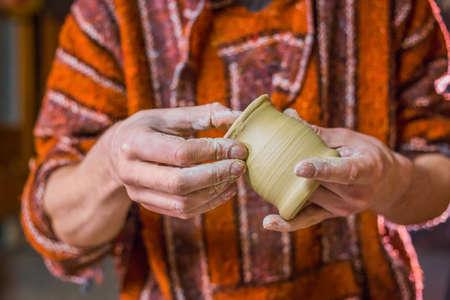 Professional male potter examining earthenware mug in pottery workshop, studio. Crafting, artwork and handmade concept Foto de archivo